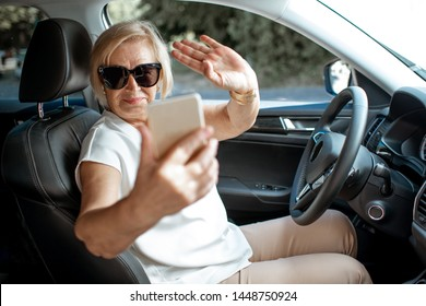 Senior business woman talking with smart phone while driving a car. Concept of an active people during retirement age
