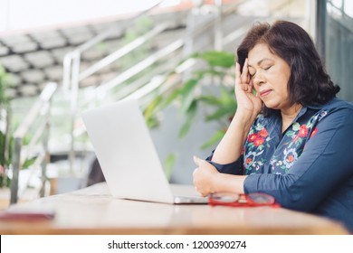 Senior Business Women with a headache.Mature woman sitting on table with laptop and touching her head with her hands while having a headache pain and feeling unwell after work.