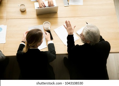 Senior businessman and businesswoman lawyer discussing contract terms at group negotiations, aged investor consulting partner considering marketing deal making decision during meeting, top view