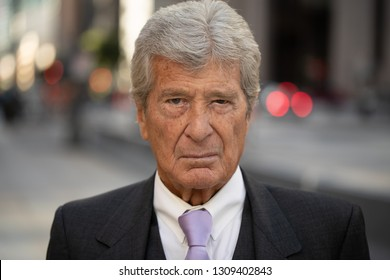 Senior businessman in city serious angry face portrait
