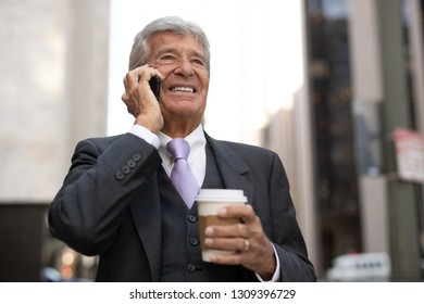 Senior businessman in city walking talking on cell phone