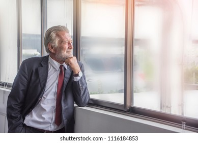Senior businessman  confident and handsome looking out of his window with a thoughtful and thinking  in office. He is in formal wear.