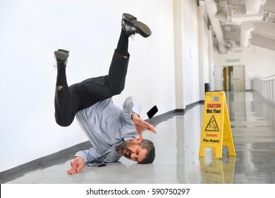 Senior businessman falling on wet floor inside office building