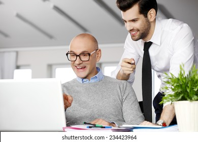 Senior businessman giving advise to his colleagues while writing annual report on laptop.