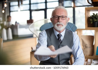 Senior businessman giving documents to you.