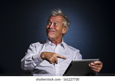 Senior businessman grinning with a look of fatuous self-satisfaction and pointing to his tablet computer with his finger as though indicating a great personal achievement, comic studio portrait