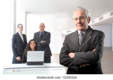 Senior businessman with group of business people on the background