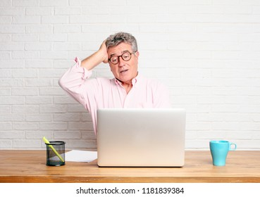 senior businessman happily realizing some good and surprising news or having a great idea, smiling with an amazed expression while touching head with hand.