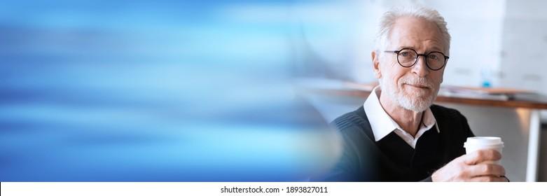 Senior businessman having a coffee break at office; panoramic banner