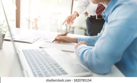 Senior Business-Mann, der neuen Mitarbeiter im Unternehmen hilft.