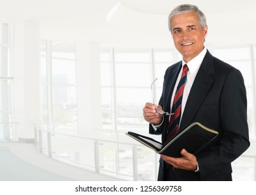 Senior Businessman in high key office setting looking at camera while holding an open notebook and his glasses.