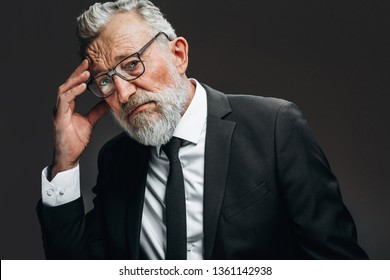 Senior businessman in his 70s with grey hair and beard having headache and rubbing temples, looking at camera with tired sorrowful eyes, isolated over black background