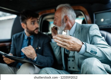 Senior businessman and his assistant sitting in limousine and working together.
