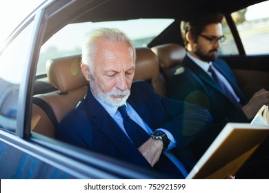 Senior businessman and his assistant sitting in limousine and working