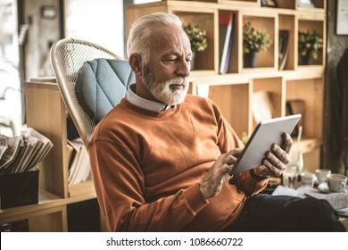 Senior businessman at his home using digital tablet.
