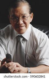Senior businessman holding mobile phone