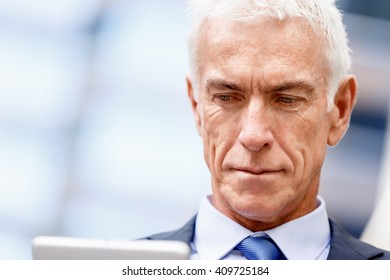 Senior businessman holding touchpad
