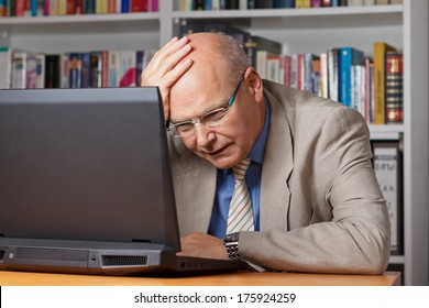 Senior businessman in jacket, shirt and tie in his office frustrateded and stressed in front of his notebook.