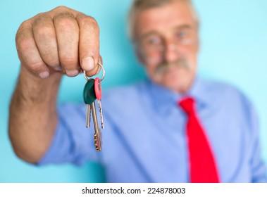 Senior businessman with keys in hand