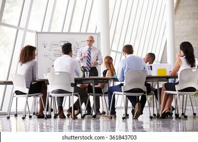Senior Businessman Leading Meeting At Boardroom Table