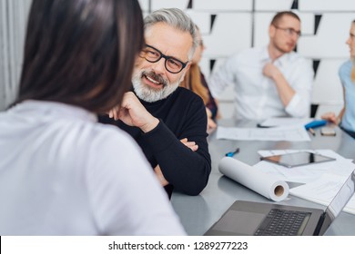 Senior businessman listening carefully to a female colleague in the office in an over the shoulder view of his face