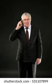 Senior businessman on black background