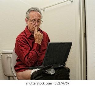 Senior businessman on toilet with laptop computer