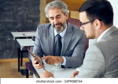 senior businessman portrait, having a discussion during a coffee lunch break