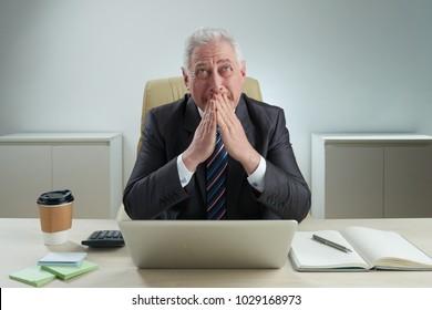Senior businessman praying at his table