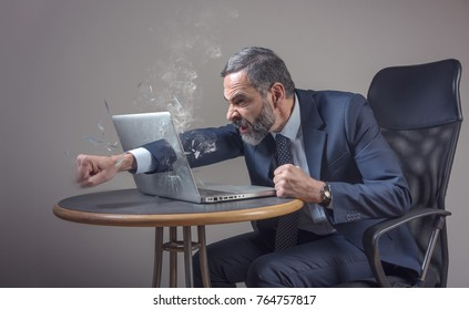 Senior businessman punching a hole through his laptop screen, furious and enraged