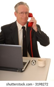 Senior businessman with a rather interesting expression on a standard telephone