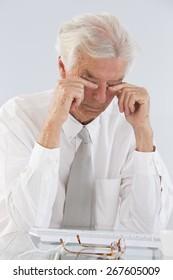 Senior Businessman Rubbing His Eyes