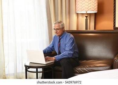 A senior businessman seated at the desk in his hotel room and working on his laptop computer. Horizontal format.