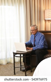 A senior businessman seated on the couch of his hotel room working on his laptop computer on a small table in front of him.