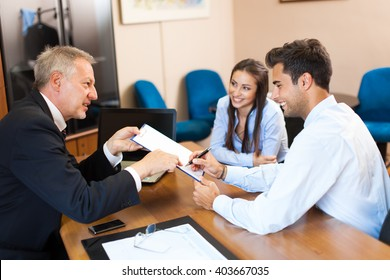 Senior businessman showing a document to sign to a couple