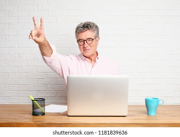 senior businessman smiling and looking satisfied and happy, counting number two with fingers.