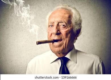 senior businessman smokes a cigar