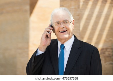 Senior Businessman Standing outside Office and Talking on Smartphone