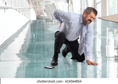 Senior businessman suffering from back injury inside office lobby