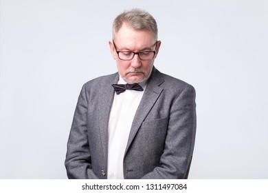 Senior businessman in suit and glasses looking down