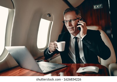 Senior businessman in suit is working on a laptop and speaking on mobile phone while flying in private jet.