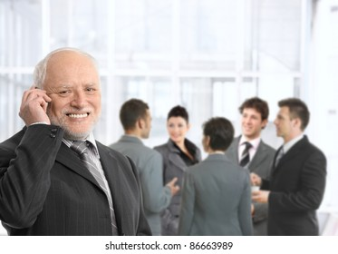 Senior businessman talking on mobile phone in office lobby, smiling, businesspeople chatting in background.?