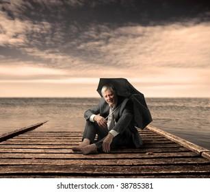 senior businessman with umbrella on a wharf