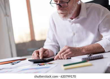 Senior businessman using a calculator in office, hard light