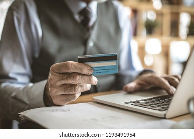 Senior businessman using laptop to check credit card . Focus is on hand.