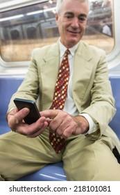 Senior Businessman Using Mobile Phone in the Subway Train
