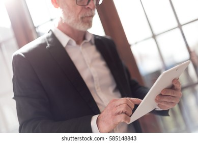 Senior businessman using tablet, hard light effect