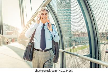 Senior businessman walking and having a conversation at phone - Portrait of mature confident smiling man wearing elegant suit