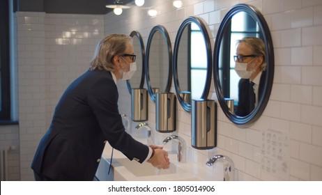 Senior businessman wearing safety mask washing hands in public restroom. Elegant confident entrepreneur in protective mask cleaning hands in sink after visiting office toilet