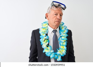Senior businessman wearing suit hawaiian lei diving goggles over isolated white background with serious expression on face. Simple and natural looking at the camera.